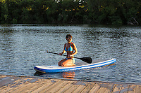 Beautiful brunette girl in turquoise bikini paddles to the dock on her paddle board on Lady Bird Lake in Austin, Texas.