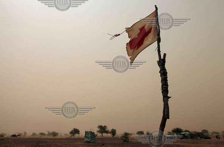 A forlorn red cross flag flies from a first aid post in a  camp at Mangaize, close to the Malian border. The camp is populated by refugees fleeing over the border to escape fighting.