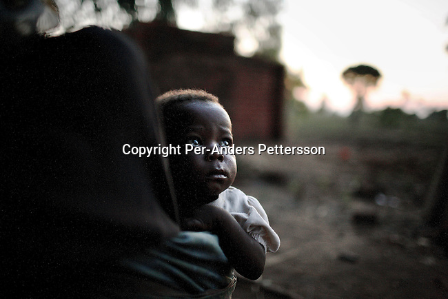 GALUFU, MALAWI NOVEMBER 12: Alex Kaliati, age 2, sits on his great grandmother Alina's back as the sun goes down on November 12, 2005 in Galufu, Malawi. Alex mother died of Aids a few months earlier. He is two years old, but underdeveloped due to lack of food, and he doesn't talk or walk, just sits around while not carried by Alina. The old woman has lost all her five daughters and some grandchildren to Aids during the last few years. She now has to take care of multiple orphans without any income. Alina harvested a bag (about 25kg) of maize during 2005 and the food only lasted for a few weeks. The village has seen an increase in poverty the last few years due to drought and HIV/Aids. Southern Africa has been hit by a severe hunger crisis due to drought and poverty and government policies. An ever-increasing HIV/Aids rate adds to the misery. Malawi is one of the worst hit areas and Galufu village is a typical small village that has become victim of this poverty spiral. (Photo by Per-Anders Pettersson)