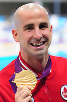 PICTURE BY ALEX BROADWAY /SWPIX.COM - 2012 London Paralympic Games - Day One - Swimming - Aquatics Centre, Olympic Park, London, England - 30/08/12 - Benoit Huot of Canada poses with his Gold Medal after winning the Men's 200m Individual Medley SM10 Final.