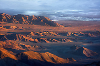 Warm sunrise light filters across the desert formations with the expanse of salt flats in the distance.