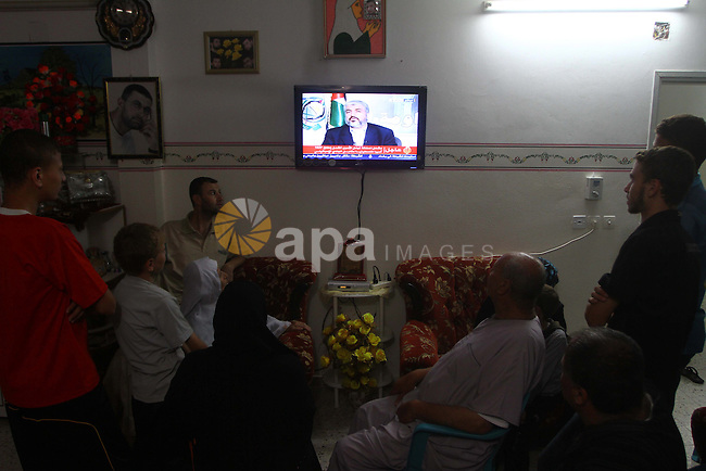 The Family of Mohammed al-Falet, watch a television broadcasting the speech of Hamas leader Khaled Meshaal, celebrating a deal that will see Palestinian detainees freed in exchange for Israeli soldier Gilad Shalit, Mohammed al-Falet a Hamas member imprisoned for life for attacks committed in Israel, in Deir al-Balah in the central Gaza Strip on October 11, 2011. Photo by Ashraf Amra