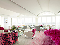 The luxurious penthouse apartment is full of edgy chic and sizzling colour.A pair of circa-1958 two-toned armchairs by Pierre Guariche flank a cocktail table by Fredrikson Stallard in the living room; the 1970s curved sofas are by Milo Baughman, and the custom-made silk shag rug is by Beauvais Carpets.