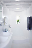 A white bathroom with beamed ceiling and moulded washbasin unit and shower.