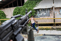 June 17, 2018: A mother and her son pass by in front of Mexican army soldiers as they look for drugs and weapons at a flying check point set up at La Sabana, a violence-plagued neighbourhood in the outskirts of Acapulco, Guerrero. A juncture of security forces, among them military, marines, federal police and local police joined under one-command to fight crime violence in the region.