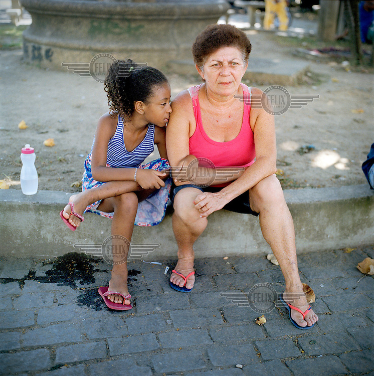 A woman and a child in the Largo do Tanque favela. Residents of Largo do Tanque have undergone forced evictions and the demolition of their homes in to make room for the Transcarioca Highway, that will eventually be built to accommodate the 2016 Olympics. In less than two weeks, 54 houses were demolished with sledgehammers and bulldozers. The city assessor sent to handle negotiations told residents not to speak with one another or seek legal advice otherwise he would reduce settlement offers. Many residents agreed to compensations of around BRL 7000 (USD 3500).