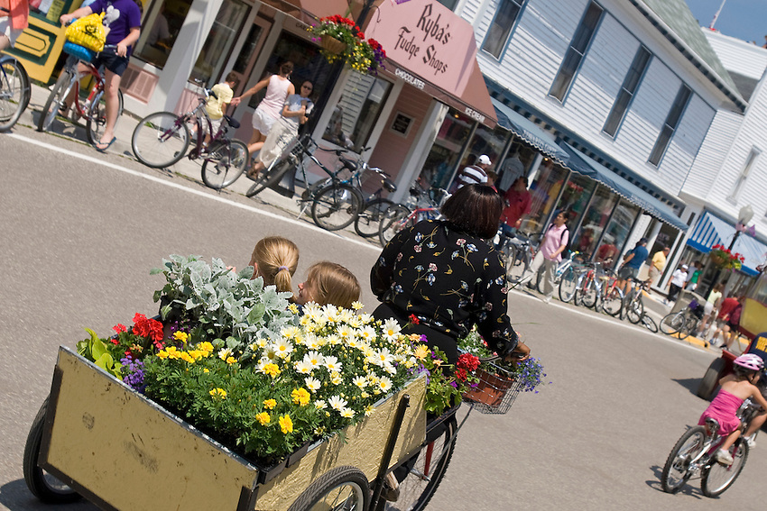 A cart full of flowers is pulled by bicycle down a street on Mackinac Island in Michigan.