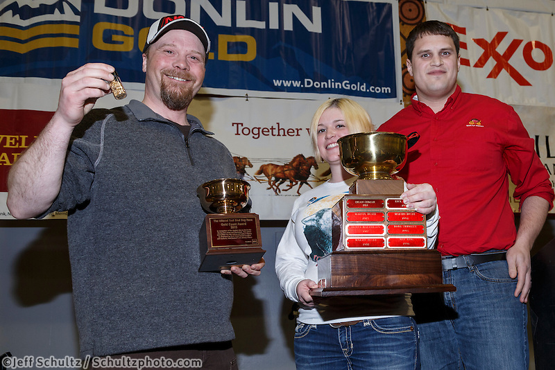 Aaron Burmeister recieves the Wells Fargo Bank Gold Coast award from Jake Slingsby and Jessica Osgood at the finishers banquet in Nome on Sunday  March 22, 2015 during Iditarod 2015.  <br /> <br /> (C) Jeff Schultz/SchultzPhoto.com - ALL RIGHTS RESERVED<br />  DUPLICATION  PROHIBITED  WITHOUT  PERMISSION