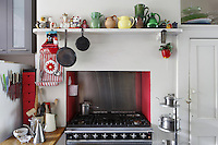 Red brings a warm glow to a kitchen and has been used in the alcove that frames the oven