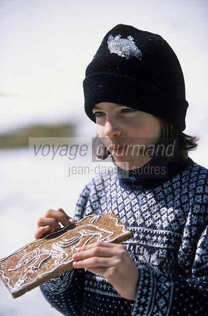 Europe/Suisse/Saanenland/Schonried: Chantal croquant un gâteau de pain d'épice à l'effigie de l'ours symbole du canton de Berg - AUTO N°316