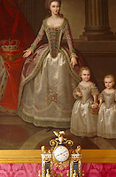 A portrait of the Duchess of Courland and two of her daughters hangs against a pink damask-covered wall