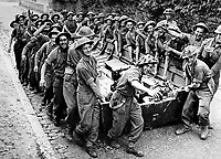 BNPS.co.uk (01202 558833)<br /> NARA/BNPS<br /> <br /> British troops carry an open plywood storm boat for the Seine River crossings in August 1944. <br /> <br /> Remarkable rarely seen photos of heroic Allied soldiers fighting their way across Europe before crossing the River Rhine 75 years ago feature in a new book.<br /> <br /> They are published in Images of War, Montgomery's Rhine Crossing, which tells the story of the legendary offensive, nicknamed Operation Plunder, in March 1945.<br /> <br /> On the night of March 23, Field Marshal Bernard Montgomery's 21st Army Group launched a massive artillery, amphibious and airborne assault to breach the historic defensive water barrier protecting northern Germany.<br /> <br /> At the same time, the Americans, with the support of the British 6th Airborne Division, set in motion Operation Varsity - involving 16,000 paratroopers - on the east bank of the Rhine. They were dropped here to seize bridges to prevent German reinforcements from contesting the bridgeheads.<br /> <br /> Fierce fighting ensued, with much bloodshed on both sides as the Allies met determined resistance from machine gun nests. But the daring operation proved successful, helping to considerably shorten the war - the Nazis surrendered just six weeks later.