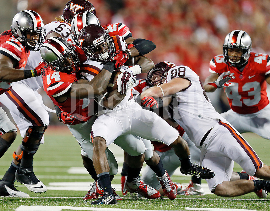 Ohio State Buckeyes linebacker Curtis Grant (14) takes down Virginia Tech Hokies running back Shai McKenzie (22) during the 2nd quarter of their game in Ohio Stadium on September 6, 2014.  (Dispatch photo by Kyle Robertson)