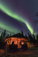 Man and woman view the northern lights above a log cabin in the Alaska Range mountains.