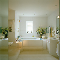 A 1980s style bathroom which has been decorated with mirrors and gilt taps and accessories with a Jacuzzi as its centrepiece