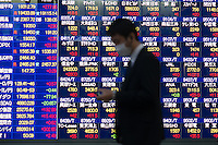 Businessmen pass a board showing the stock values  Tokyo, Japan. Japan's benchmark gauge has climbed 10 percent this year, the best performance among developed Asian stock markets, as buying by the central bank and the nation's $1.1 trillion pension fund buoyed shares<br /> March-2015