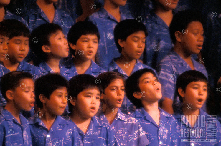 Close-up of a dozen young, dark-haired local boys in blue aloha shirts performing with the Honolulu Boys Choir.