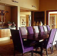In the dining room the large table seats fourteen and the chairs around it are upholstered in deep purple and violet, vivid against the yellow ochre of the walls
