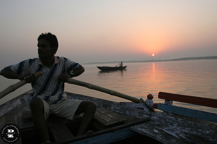 A man rows a boat on the calm waters of  the Ganges (Ganga) River as the morning sun rises in the distance.  For Hindus, the Ganges is the most sacred river in India.  Hindus believe that the Ganges purifies all those who bathe in her waters, cleansing them of all their sins.  Photograph by Douglas ZImmerman