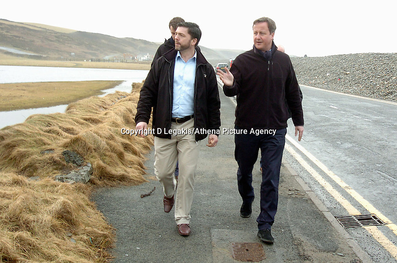 Pictured L-R: Pembrokeshire MP Stephen Crabb and Prime Minister David Cameron walking by the storm damaged coastal road in Newgale, Pembrokeshire. Wednesday 19 February 2014<br /> Re: Prime Minister David Cameron has today visited the Pembrokeshire village of Newgale which suffered severe damage during the early January and February storms.