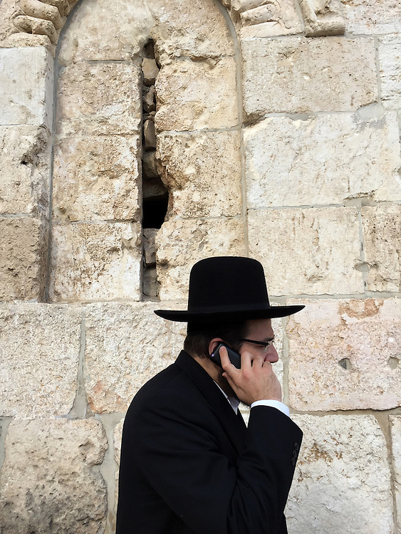 5. &quot;Hasid (ultra-orthodox Jew) on Cell Phone&quot;:  outside walls of the Old City, Jerusalem.<br /> <br /> At last we arrived in Jerusalem: the holiest city in the Holy Land. A Hasidic ultra-orthodox family was walking past the Old City's stone walls; father (the patriarch) on a cell phone, wife and sons at his side.<br />  <br /> According to Marc Rosenstein, an Israeli historian who is currently writing about my photographs, &quot;The dissonance between the 'heavenly' and the 'earthly' Jerusalem&quot; is perhaps the most pervasive of the oppositions that characterize Israel today. The issue, as Marc (and I) see it, is that there is an undeniable contradiction between what Jewish liturgy calls &quot;the first flowering of our redemption,&quot; and &quot;the presence of urban blight, pollution, corruption -- or even just of people going about their normal, quotidian, unmessianic lives....&quot; This &quot;compels attention,&quot; writes Marc. And I agree, having come to Israel on a spiritual quest to honor my parents, and now encountering so much more.