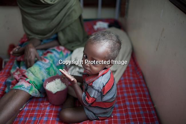 WAJIR, KENYA - JULY 6: Makay Bashane, age 40, with her child Abdirahim Abdullah, age two, eat rice after being admitted to the stabilization center in Wajir on July 6 in central Wajir, Kenya. The child was referred to the stabilization center in Wajir by Save the Children. Two successive poor rains, entrenched poverty and lack of investment in affected areas have pushed millions of people into a fight for survival in the Horn of Africa. This is the driest this area has been since sixty years. People in smaller town are usually fortunate to have water. In rural areas, most wells has dried up and some people was as much as eight kilometers to fetch water. Most of the livestock has perished and the remaining stock has often been taken far away for better conditions. Many has even crossed into neighboring Somalia for better pasture. (Photo by Per-Anders Pettersson)