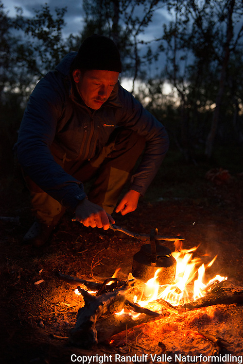 Mann med kaffekjel foran bålet. ---- Man with coffe pot in front of camp fire.