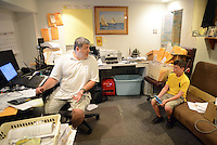 Jeffrey Gunn (left), speaks in his home office with his son Colt Gunn, 11 as he plays a video game Friday June 19, 2015 in Bensalem, Pennsylvania. For the past 15 years, Gunn has worked out of his home in his job with Meridian. (Photo by William Thomas Cain)