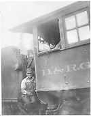 Close up of fireman on locomotive steps and sleeping engineer in cab.<br /> D&amp;RG