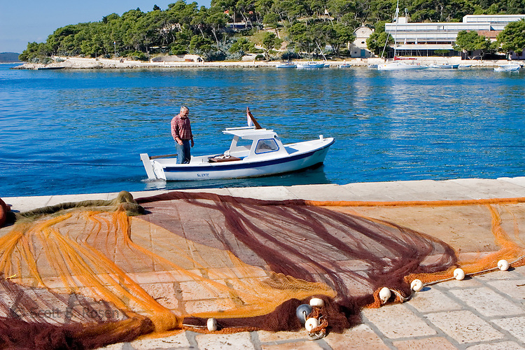 Croatian fisherman on small boat entering harbor, with net drying in the foreground, Hvar Island, Croatia