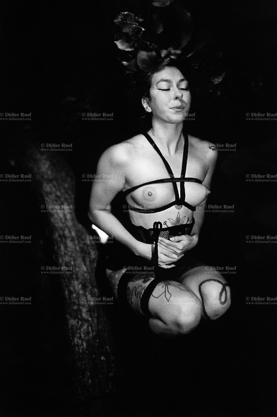 """Switzerland. Canton Valais. Bas-Valais. Shibari at night in the forest. A nude woman with tattoos is tied with ropes on a tree's trunk. The contemporary meaning of Shibari describes an ancient Japanese artistic form of rope bondage. The art of erotic bondage, called Shibari, is an art of erotic spirituality. Shibari style rigging creates geometric patterns and shapes with rope that contrast beautifully with the human body's natural curves. The ropes and their texture provide contrast to smooth skin and curves. In Shibari, the model is the canvas, the rope is the paint and brush, and the rigger is the rope artist. Shibari experience results in an increased level of endorphins and other hormones, creating a trance-like experience for the model. When a Shibari scene is performed with appropriate ambience, these effects are actually visible in the face of the model. The term """"rope drunk"""" is sometimes affectionately used to describe the euphoric condition of the model after a Shibari experience. 23.07.2016 © 2016 Didier Ruef"""