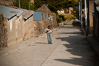 A man walks down a street outside of the town of Lari. The typical homes in the Colca Valley are made from tin roofs and adobe (mud and straw).  Visitors to the villages of the Colca Canyon are reminded of how life used to be in a simpler time.