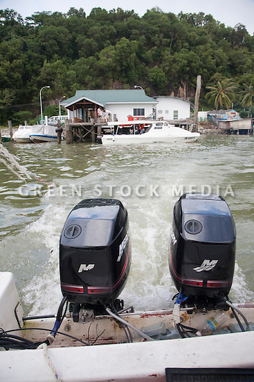 Boat with two outboard motors leaving a dock.