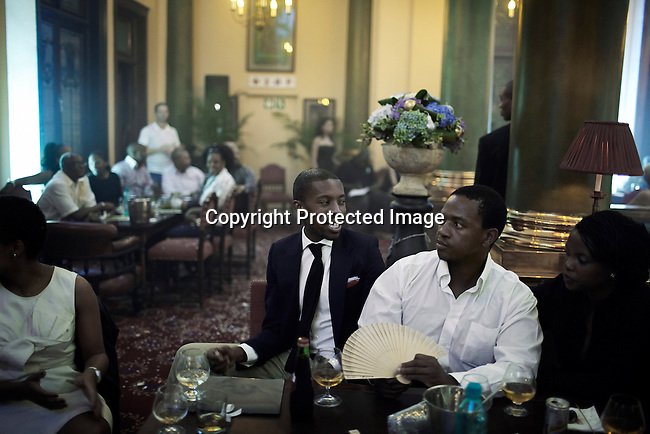 JOHANNESBURG, SOUTH AFRICA - FEBRUARY 16: Wealthy black South Africans wait for the Klûk CGDT label fashion show at the Rand Club at Joburg Fashion Week on February 16, 2011, in Johannesburg, South Africa. Klûk CGDT, created by the designers Malcolm KLûK and Christiaan Gabriel Du Toit and their brand is not so much about clothes, but rather life and a holistic experiential, boundary blurring approach to style that encompasses all the senses. Trends influencing their collection include touches of tribal, vintage and the baroque. Their couture collection only to order. The event was held at the Rand Club, A former private all male club during the Apartheid era. Here, the wealthy industrialists of the country networked, wined and dined. The club now allows female members. To see newly wealthy black people in the club is a sign on the new South Africa. (Photo by Per-Anders Pettersson)