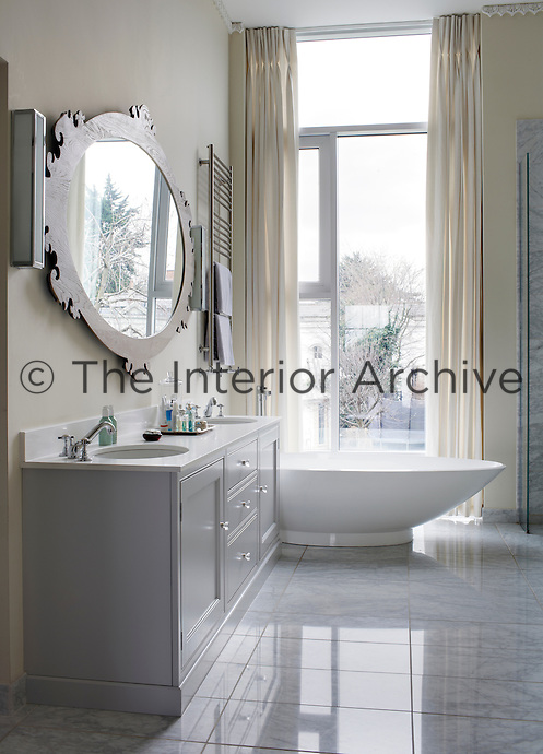 A master ensuite bathroom with matching sinks and contemporary slipper bath.