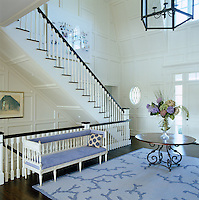 In the double-height entrance hall a blue coral-patterned rug stands out against dark floorboards and ivory-painted panelling