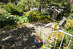 A small flagstone patio surrounded by gardens offers a peaceful place to relax.