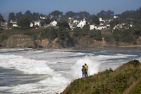 Couple standing on the cliffs overlooking Big River and the town of Mendocino, Mendocino California