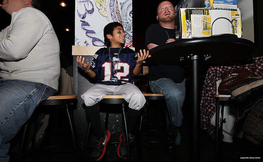 Oscar Foye, 10, of Kittery, left, watches in dismay with Graham Gardner, right, of Rhode Island as the New England Patriots lose to the Ravens at the Buffalo Wild Wings sports bar in Newington, N.H., Sunday, Jan. 20, 2013. (Portsmouth Herald Photo Cheryl Senter)