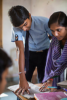 Adarsh Patidar, aged 15, speaks to his teacher in class in Vasudha Vidya Vihar school in Khargone, Madhya Pradesh, India on 12 November 2014. Adarsh, the son of a Fairtrade Cotton Producer, wants to follow in his father's footsteps and become a cotton farmer. The school was built using the Fairtrade Premium of the Fairtrade Cotton Producers. Photo by Suzanne Lee for Fairtrade