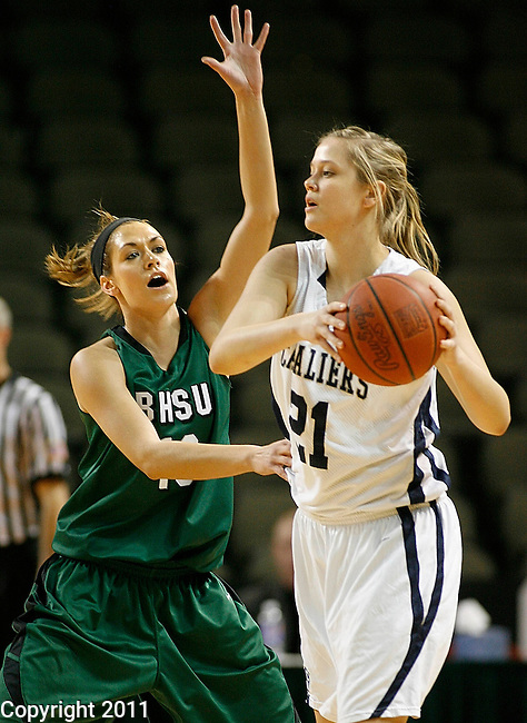 SIOUX CITY, IA -- March 10, 2011 -- Morgan Mines #10 of Black Hills State pressures Grace Cappleman #21 of Concordia University (OR) during their opening round game at  the 2011 NAIA Division II Women's Basketball National Championship in Sioux City, IA Thursday. (Photo by Dick Carlson/Inertia)