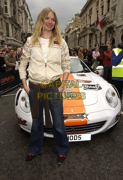 JODIE KIDD.At the Photocall for the Launch of Gumball Rally 3000, Pall Mall, London, England, April 30th 2006..full length cream beige jacket hands in pockets jeans trainers black and orange car.Ref: CAN.www.capitalpictures.com.sales@capitalpictures.com.©Can Nguyen/Capital Pictures