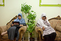 Campaign trail: Muslim sisters Oumayma Kamel and Heba Hassan take a break during a visit to the village of Al Saf, Cairo in June 2012. Kamel's laptop shows a sticker for Freedom and Justice Party candidate Mohammed Morsi, elected shortly afterwards as Egyptian president. Kamel is now a senior adviser to Morsi. Al Saf village, Egypt. June 13th, 2012