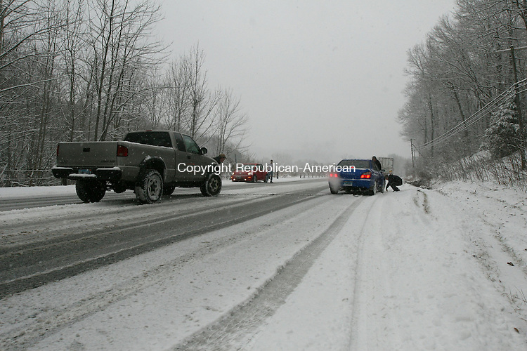 """HARWINTON, CT - 28 January, 2010 - 012810MO03 - Two passing motorists came to the aid of Harwinton resident Mike Borla, 17, who lost control of his Subaru and wound up in a ditch off of Route 4 Thursday. Rick Clark, 50, of Torrington is at the wheel of the Chevrolet pickup pulling Borla's car at left. Mike McAllister, a driver for New England Bark Mulch, also stopped his tractor trailer to help. """"You see someone in trouble, that's what you do,"""" McAllister said. Jim Moore Republican-American."""