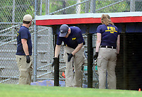 Evidence technicians from the FBI comb through the crime scene for evidence in front of the third base dugout where  a gunman opened fire on members of Congress who were practicing for the annual Congressional baseball game in Alexandria, Virginia on Wednesday, June 14, 2017. Photo Credit: Ron Sachs/CNP/AdMedia