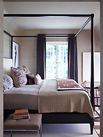 In the stylish master bedroom, a four-poster bed by Hickory Chair is dressed in Restoration Hardware linens; the curtains are of a Ralph Lauren Home fabric, and the artwork is by Robert Longo.