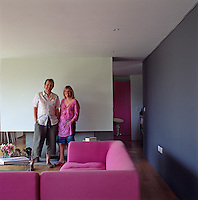 David Atwood and Jane Tranter stand by the fireplace in their living room