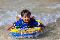 Young Local Hawaiian boy bodyboarding at the beach on Oahu, Hawaii