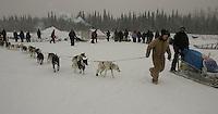 Volunteer dog handler Cathy Lieser helps Doug Swingley park his team at the Nikolai checkpoint