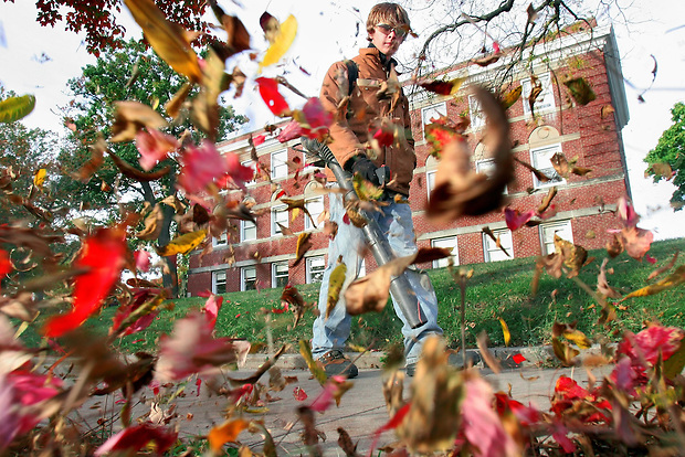Groundskeeper David Pendras of New Virginia blows leaves from a walkway in front of Howard Hall on the Drake University Campus.